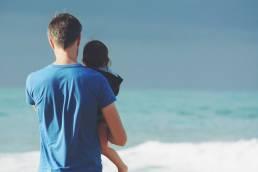 father child windy beach
