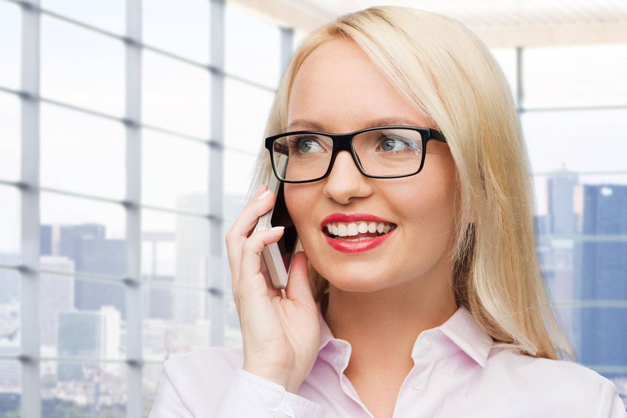 blonde woman wearing glasses and talking on phone in city building