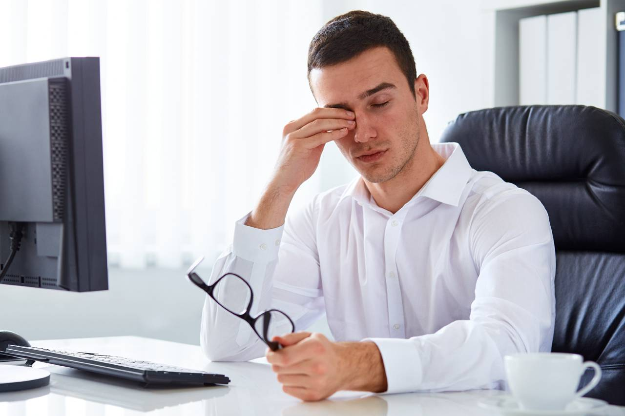 man rubbing his eyes due to dry eye syndrome