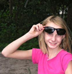 Girl looking out from forest with raised glasses