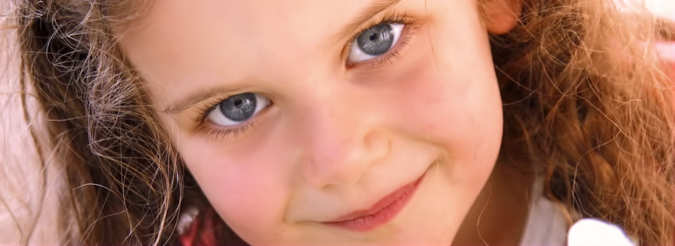 close up of blue eyed blond child slide