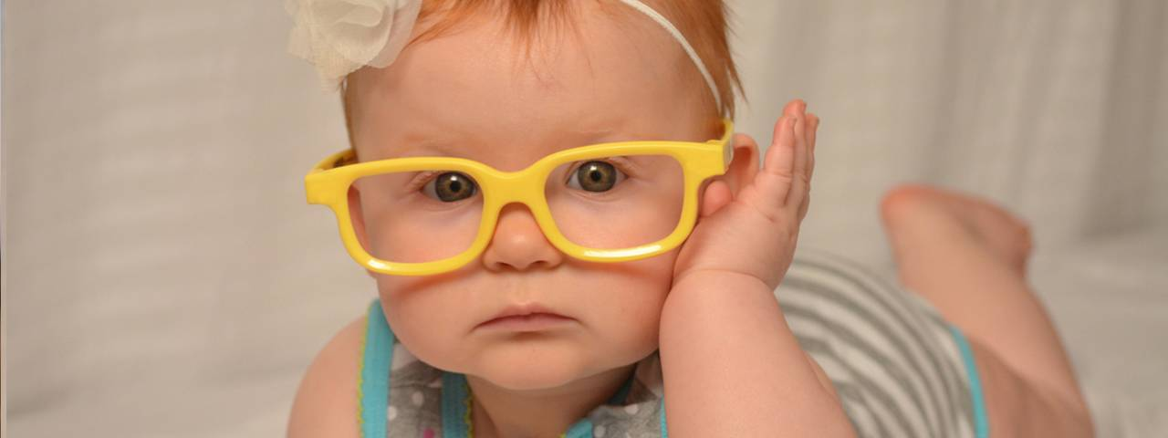 baby girl yellow glasses closeup 1280x480