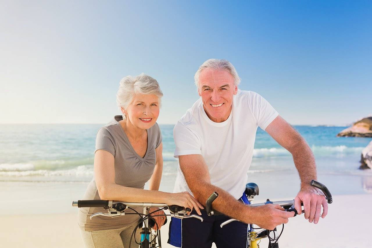 older man and woman on beach advertising eye care
