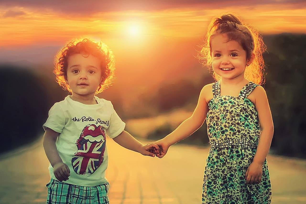 children holding hands glowing sun