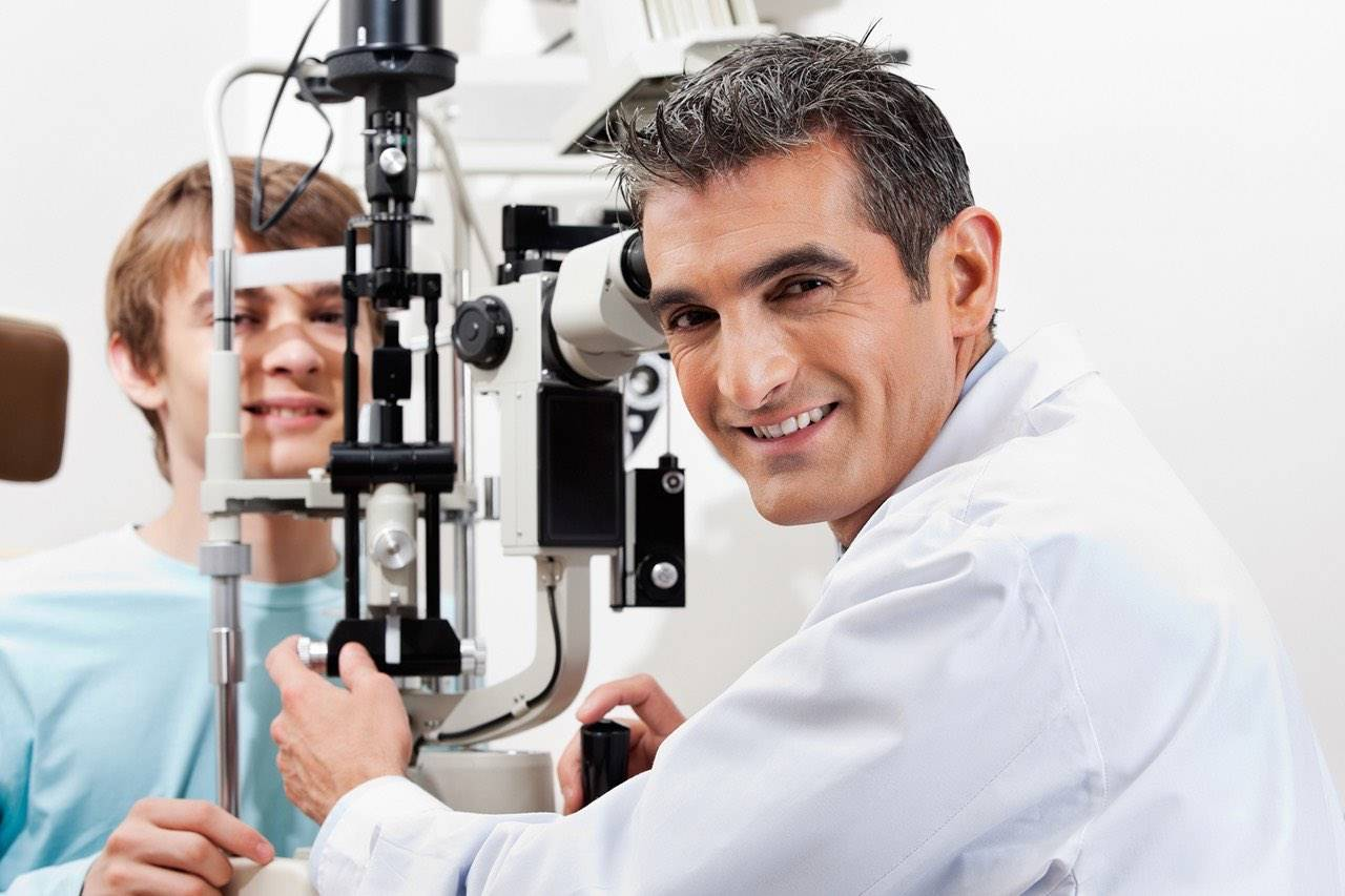 optometrist giving eye exam to boy in Round Rock, TX