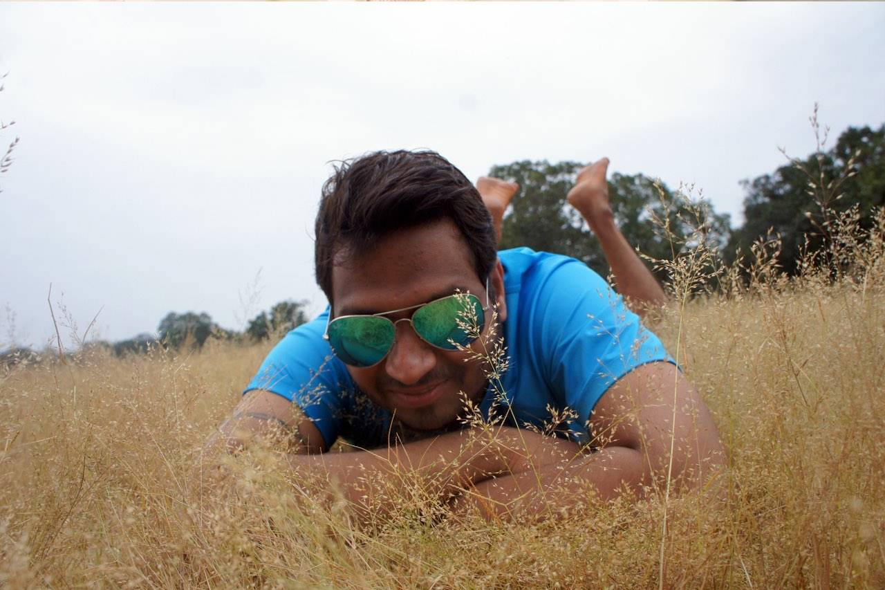 man in grass with sunglasses