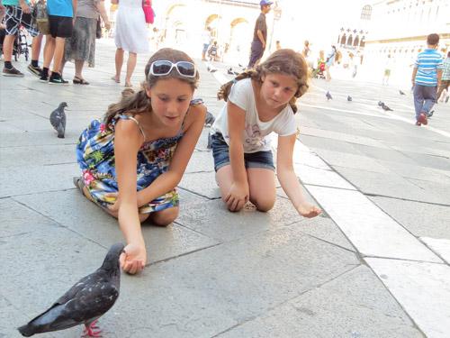 girls feeding pigeon