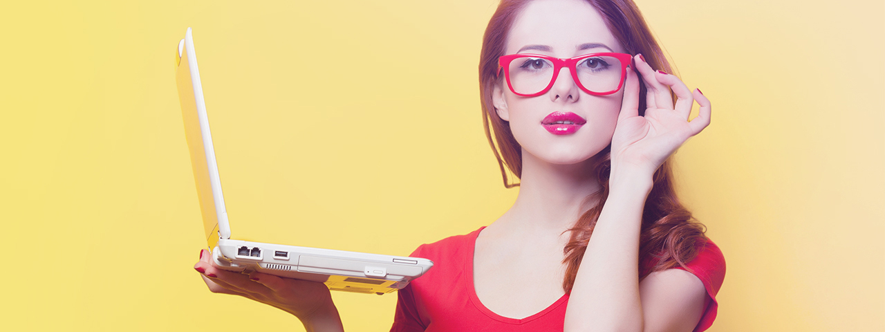 a woman holding a laptop red glasses