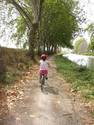 little girl riding bike along path